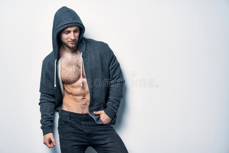 Brutal naked muscular man dressed in a grey hoodie stock photo