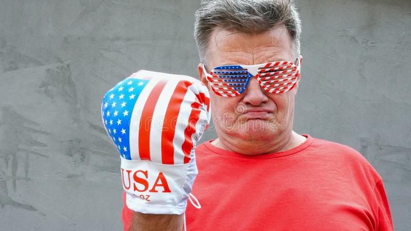 Brutal, proud, caucasian ethnicity senior man in glasses in the colors of American flag. He threatens someone with his fist in. Boxing glove. Close-up stock photos
