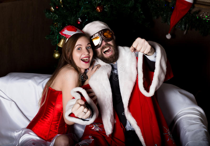 Brutal Santa Claus with female nurse woman in carnival costume, driving on couch like on a car stock photos