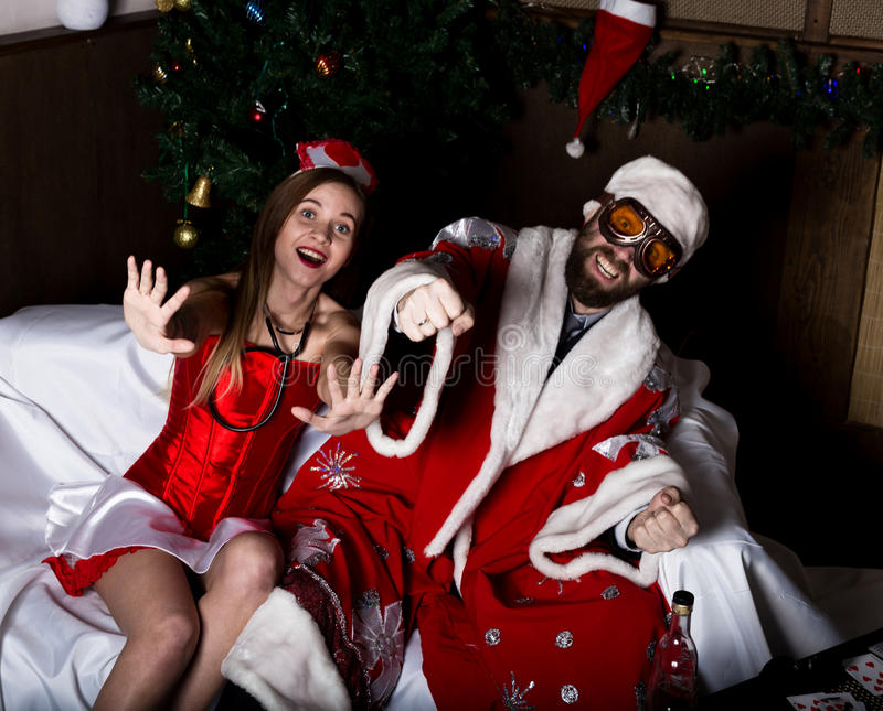 Brutal Santa Claus with female nurse woman in carnival costume, driving on couch like on a car stock images