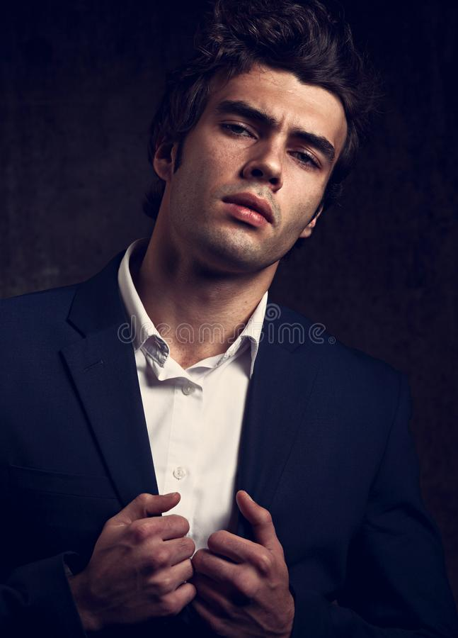 Brutal serious business man posing in blue suit and white style royalty free stock image