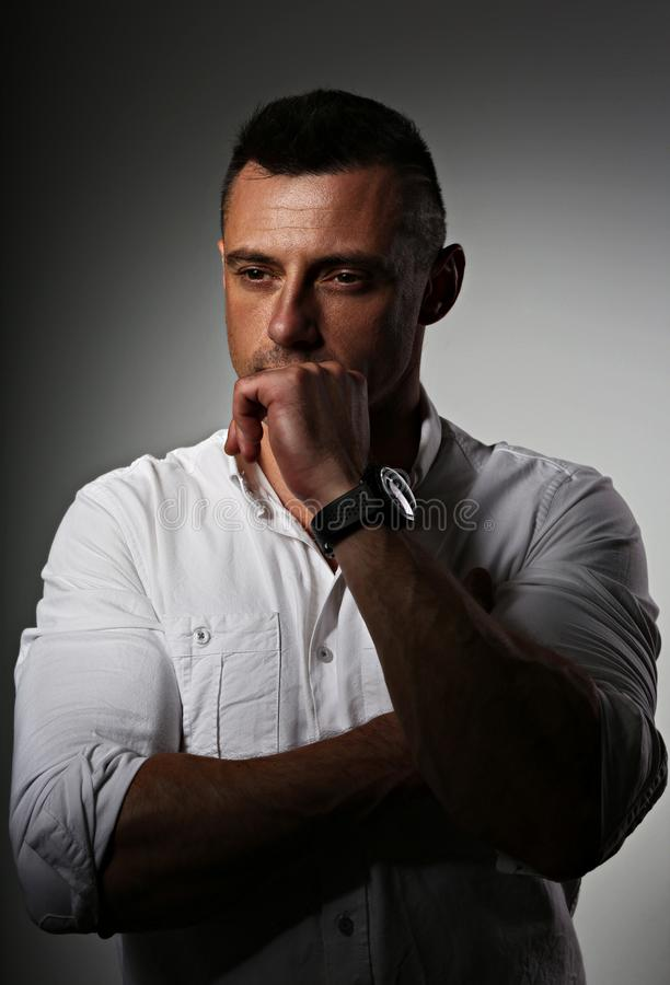 Brutal serious business man thinking in white style shirt on grey dark shadow background. Closeup portrait stock image