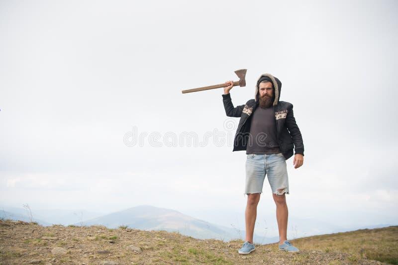Brutal skäggig hipster för man med yxaställningen på bergöverkant royaltyfri fotografi