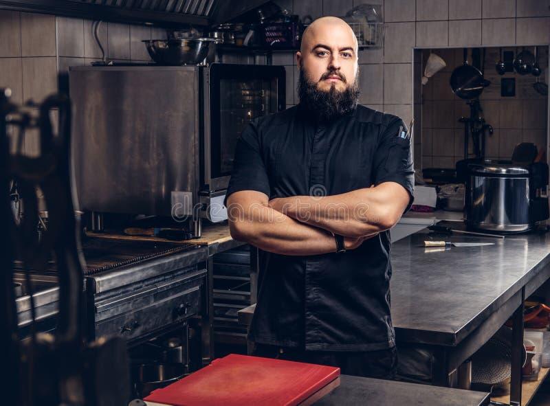 Brutal skäggig kockkock i svart enhetligt anseende med korsade armar i köket royaltyfri foto