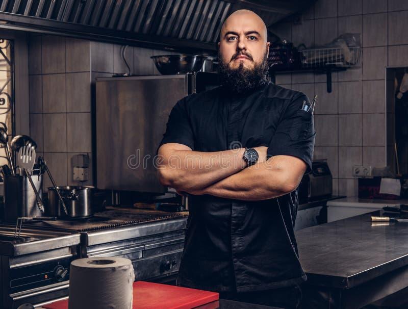 Brutal skäggig kockkock i svart enhetligt anseende med korsade armar i köket royaltyfri fotografi