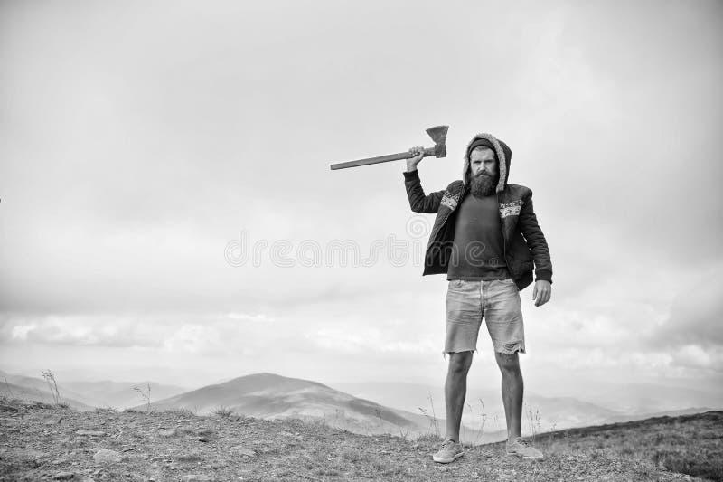 Brutal skäggig man för skogsarbetare med yxaställningen på bergöverkant arkivfoton