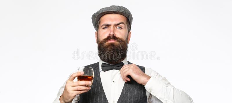 Brutal skäggig man med exponeringsglas av whisky, konjak, konjak Attraktiv man med en konjak Gammal hipsterstil whiskey royaltyfria bilder