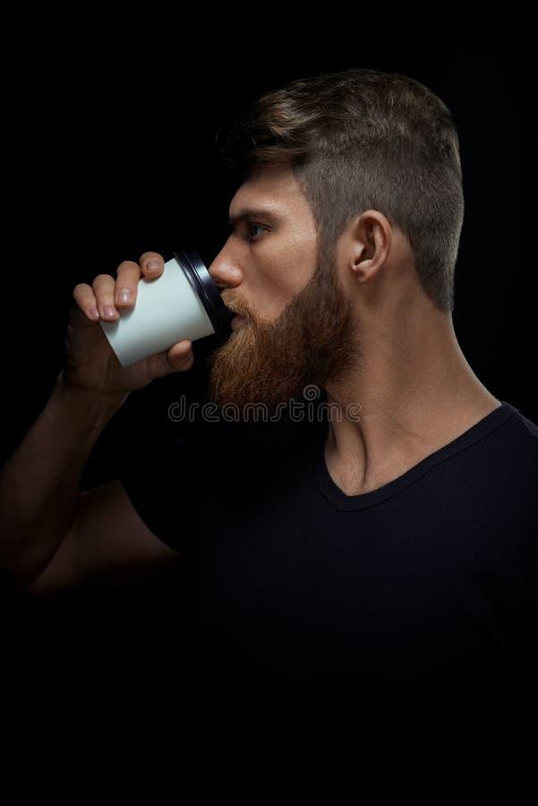 Brutal skäggig man som dricker kaffe för att gå royaltyfria bilder