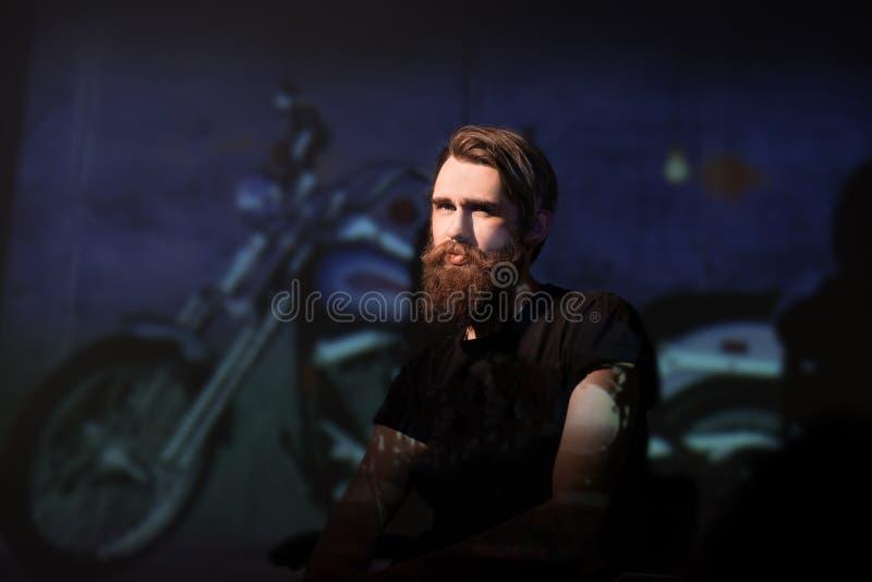 Brutal skäggig mancyklist som sitter i en stol royaltyfri fotografi