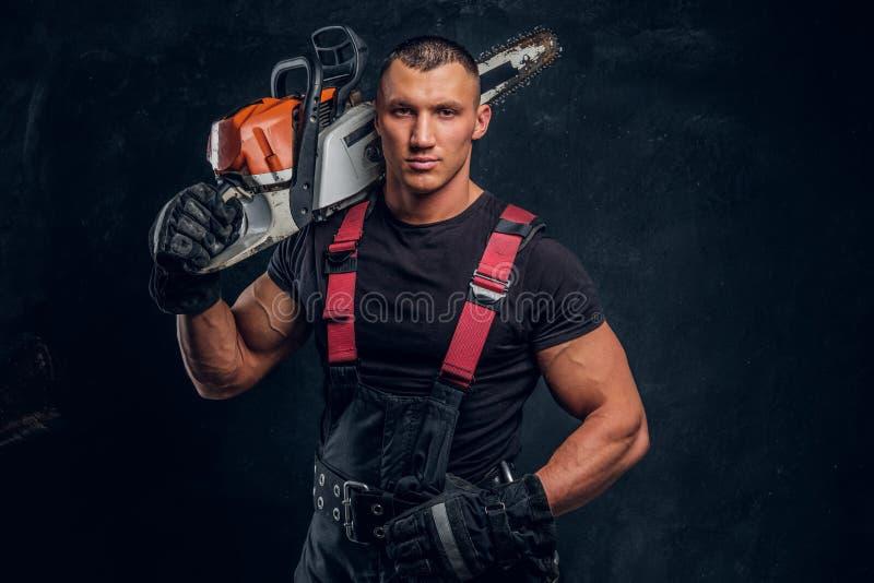 Brutal skogsarbetare som poserar med en chainsaw på hans skuldra och ser en kamera med en säker blick arkivfoton