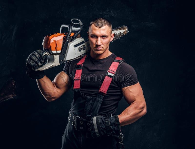 Brutal skogsarbetare som poserar med en chainsaw på hans skuldra och ser en kamera med en säker blick fotografering för bildbyråer