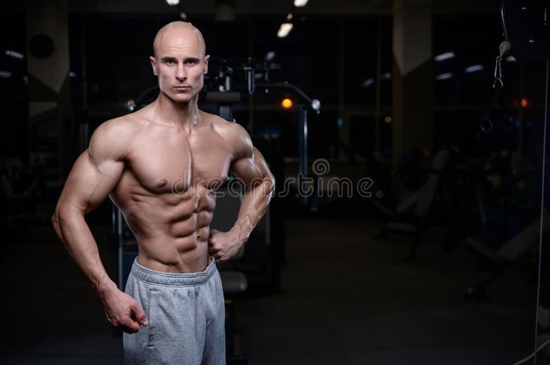 Brutal strong bodybuilder athletic men pumping up muscles with d. Bald brutal strong bodybuilder athletic fitness man pumping up abs muscles. Workout stock photos