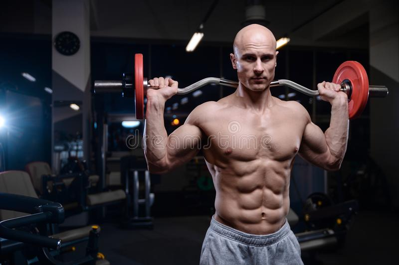Brutal strong bodybuilder athletic men pumping up muscles with d. Bald brutal strong bodybuilder athletic fitness man pumping up abs muscles. Workout royalty free stock image