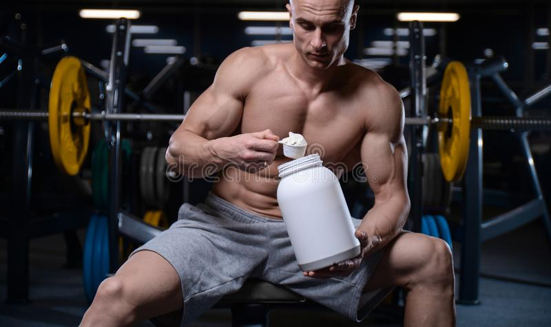 Brutal strong bodybuilder athletic men pumping up muscles with d. Bald brutal strong bodybuilder athletic fitness man pumping up abs muscles. Workout royalty free stock photo