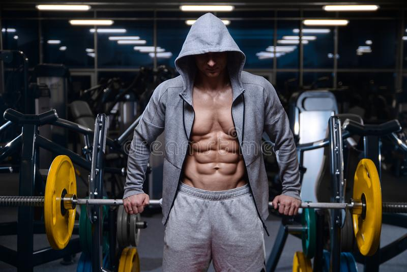 Brutal strong bodybuilder athletic men pumping up muscles with d. Bald brutal strong bodybuilder athletic fitness man pumping up abs muscles. Workout stock photography