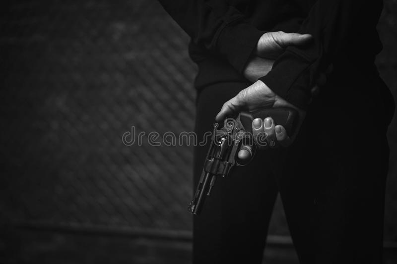 Brutal vicious criminal waiting for his victim. Patient and dangerous. Senseless felonious mad man standing on a dark street holding a gun and hiding it behind stock photography