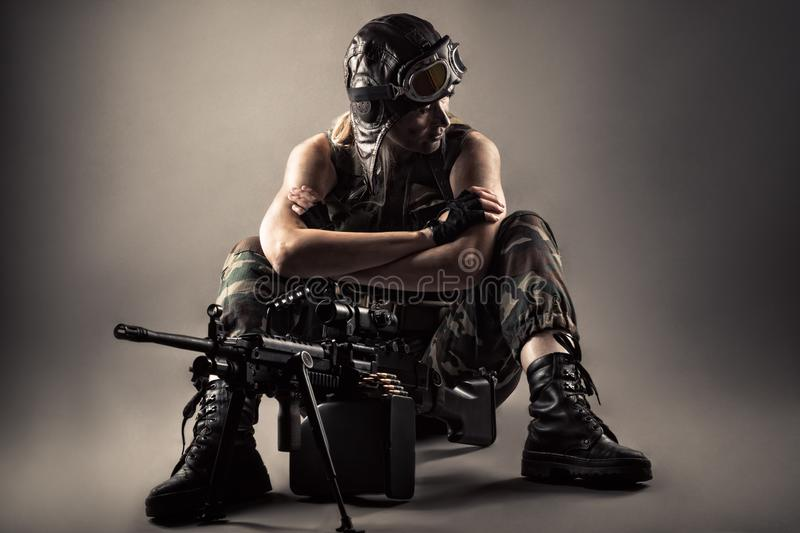 Brutal woman sitting on floor with machine gun stock images