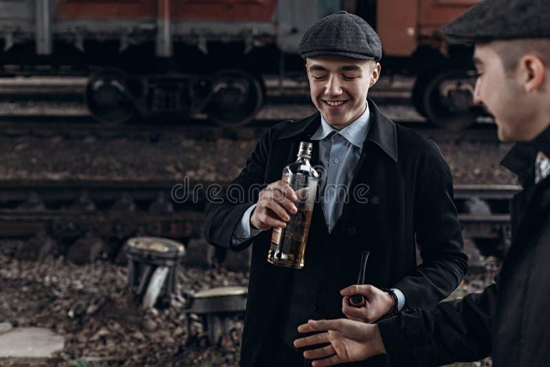 Brutala gangster som dricker på bakgrund av den järnväg vagnen en royaltyfri bild