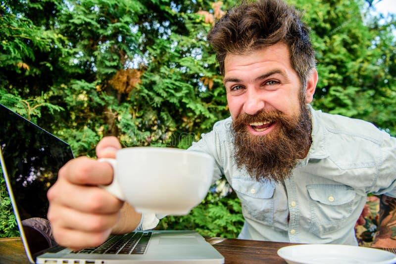 brutale gebaarde hipster bij koffiepauze Gelukkige mens met laptop Behendige zaken Bedrijfs succes Op groene achtergrond stock foto's