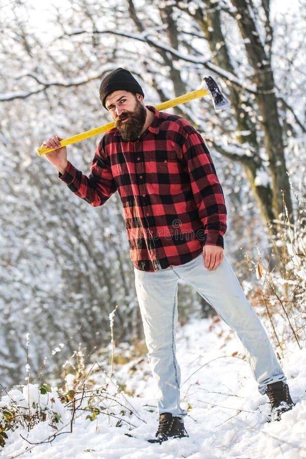 Brutale gebaarde mens met baard en snor op de winterdag, sneeuw bos Knappe mens, hipster, houthakker aantrekkelijk stock afbeelding