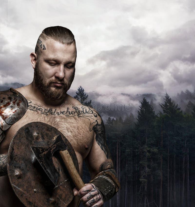 Brutale getatoeeerde mannelijke Viking met bijl en schild royalty-vrije stock fotografie