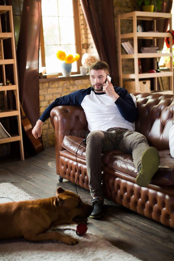 Brutale jonge mensenzitting in bank die thuis op telefoon spreken royalty-vrije stock foto