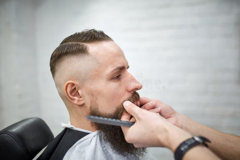 Brutale kerel in moderne Barber Shop De kapper maakt tot kapsel een mens met een lange baard De hoofdkapper doet kapsel royalty-vrije stock foto
