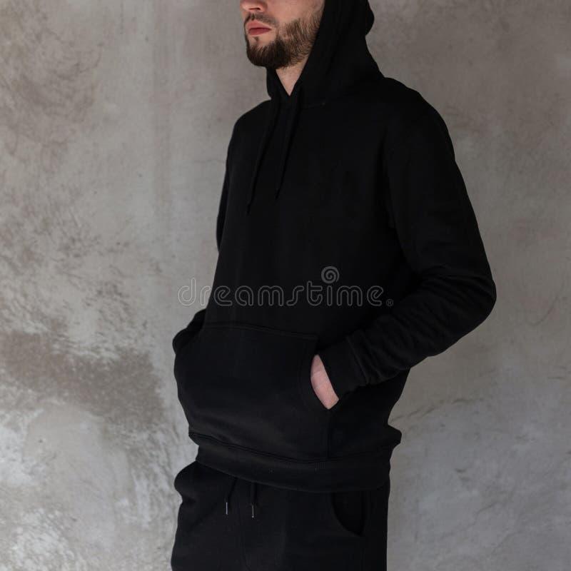 Brutale knappe jonge hipstermens met een baard in een zwart modieus sweatshirt met een kap in het zwarte in jeans stellen stock afbeelding