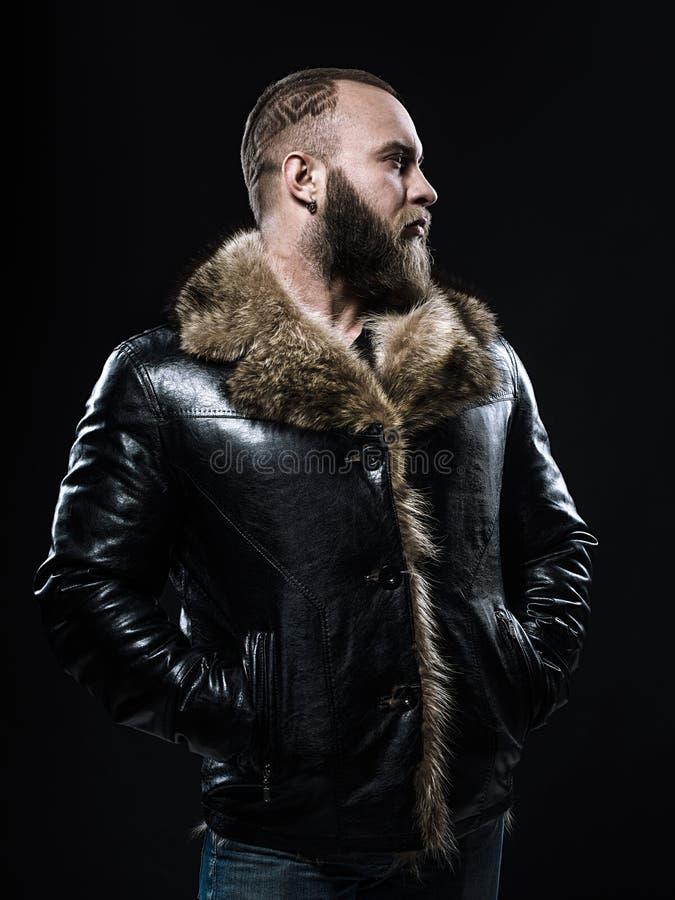 Brutale knappe ongeschoren mens met lange baard en snor in bl stock fotografie
