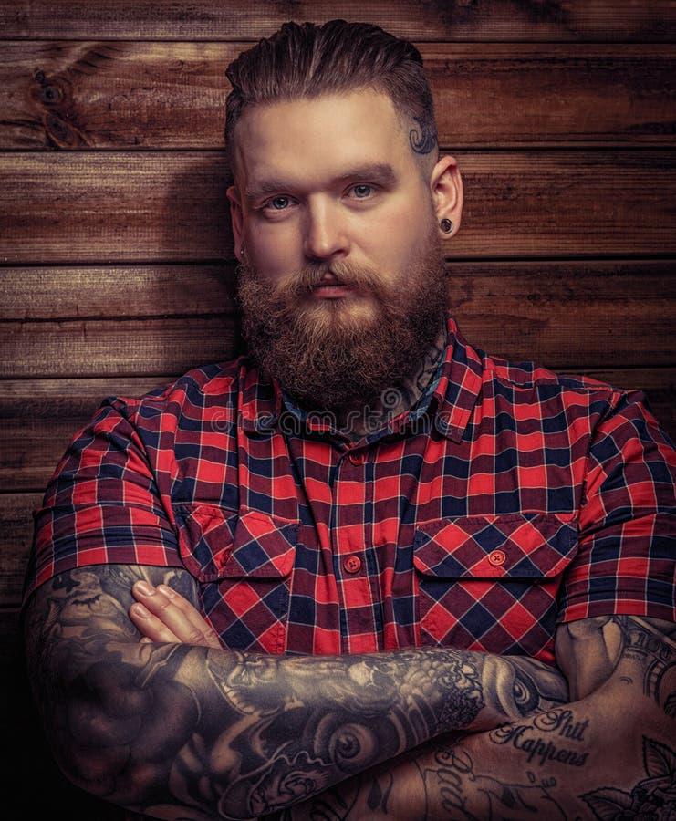 Brutale mens met tatoegeringen en baard stock foto
