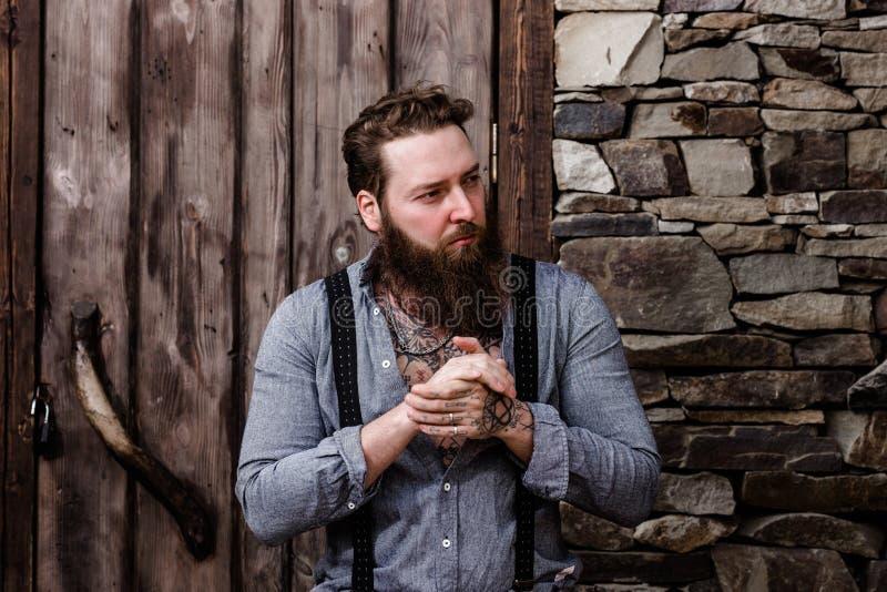 Brutale sterke mens met een baard en tatoegeringen op zijn handen gekleed in modieuze vrijetijdskledingstribunes op de achtergron royalty-vrije stock afbeelding
