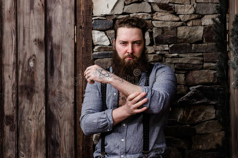 Brutale sterke mens met een baard en tatoegeringen op zijn handen gekleed in modieuze vrijetijdskledingstribunes op de achtergron royalty-vrije stock afbeeldingen