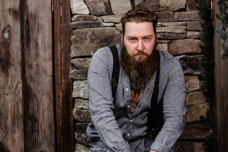 Brutale sterke mens met een baard en tatoegeringen op zijn handen gekleed in modieuze vrijetijdskledingstribunes op de achtergron royalty-vrije stock fotografie