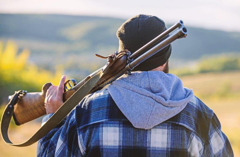 : Brutalidad y masculinidad El cazador lleva el arma del rifle en parte posterior del hombro imagen de archivo