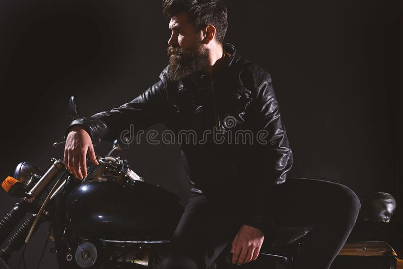 Brutality and masculine concept. Man with beard, biker in leather jacket lean on motor bike in darkness, black. Background. Macho, brutal biker in leather stock images