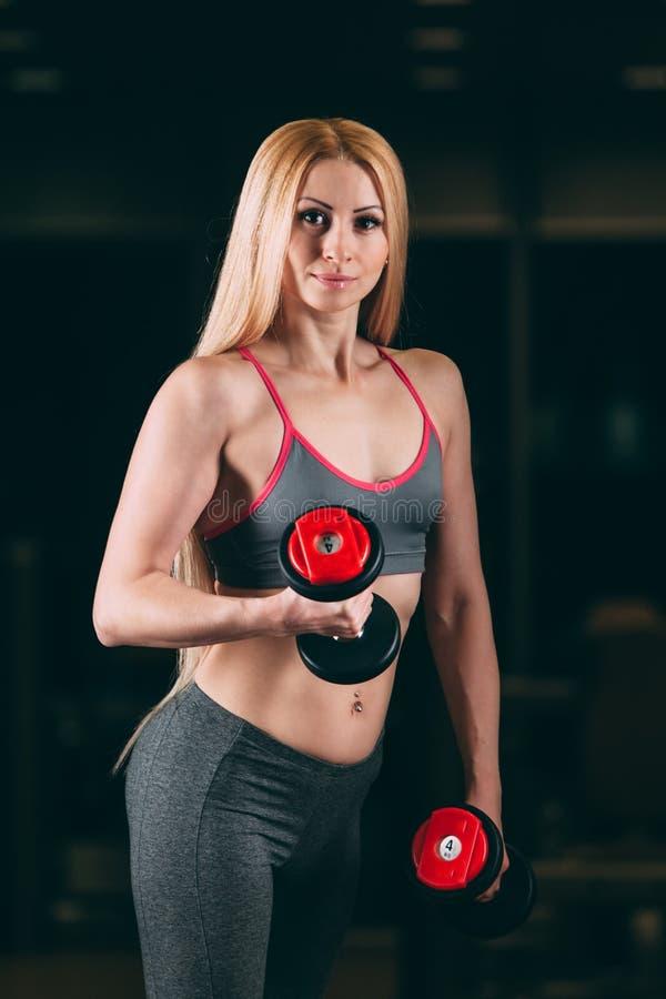 Brutalna sportowa kobieta pompuje up mięśnie z dumbbells w gym zdjęcie stock