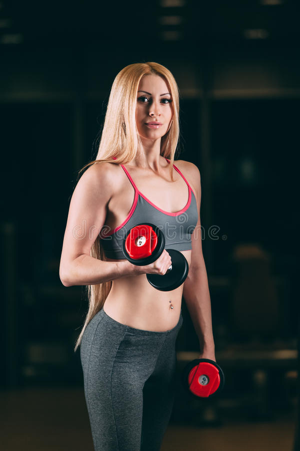 Brutalna sportowa kobieta pompuje up mięśnie z dumbbells w gym fotografia royalty free