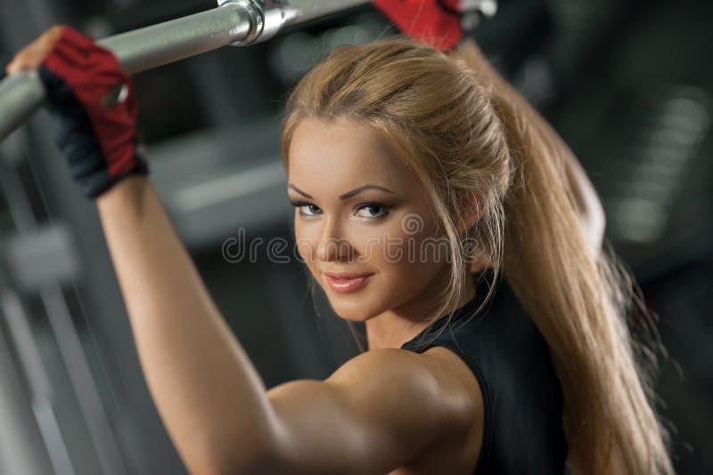 Brutalna sportowa kobieta robi tylnym pullups przy gym zdjęcie royalty free