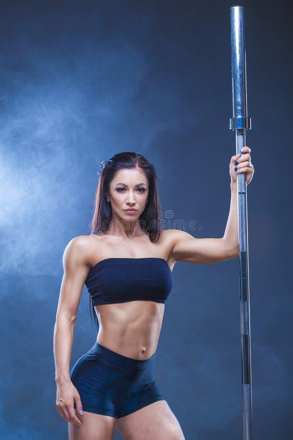 Brutalna sportowa seksowna kobieta trzyma barbell Pojęcie ćwiczenie bawi się, reklamujący gym Na czerni zdjęcia royalty free