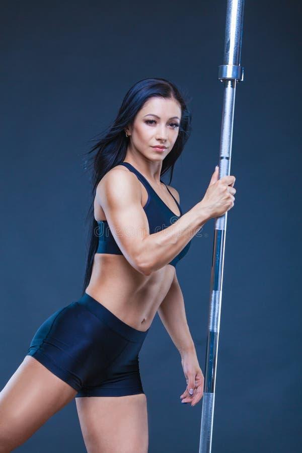 Brutalna sportowa seksowna kobieta trzyma barbell Pojęcie ćwiczenie bawi się, reklamujący gym odizolowywający na czerni fotografia royalty free