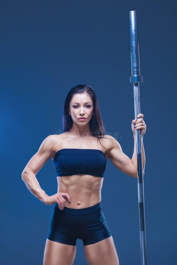 Brutalna sportowa seksowna kobieta trzyma barbell Pojęcie ćwiczenie bawi się, reklamujący gym odizolowywający na czerni obrazy stock