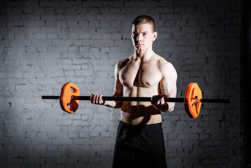 Brutalnego bodybuilder sportowy mężczyzna z perfect abs, ramion, bicepsów, triceps i klatki piersiowej Deadlift barbells treningi zdjęcia stock