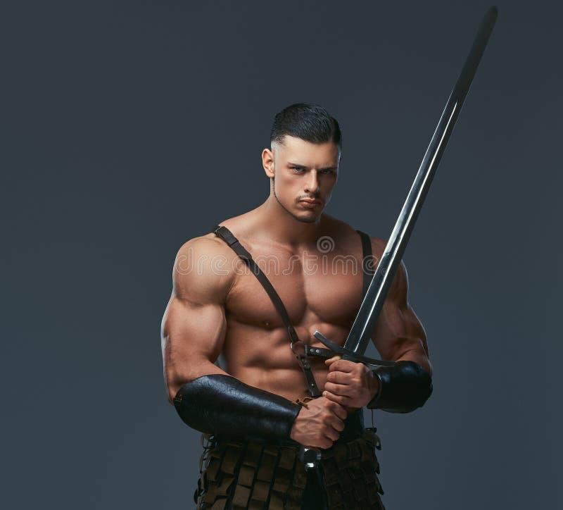 Brutalny antycznego Grecja wojownik z mięśniowym ciałem w batalistycznych mundurach fotografia stock