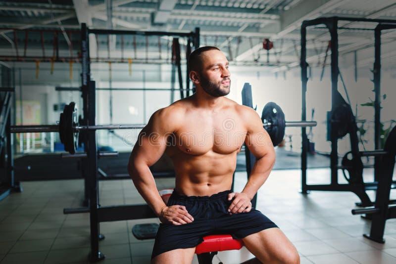 Brutalny bodybuilder obok barbells Potomstwo sportów mężczyzna z sześć paczek abs na gym tle Styl życia aktywny pojęcie zdjęcia stock