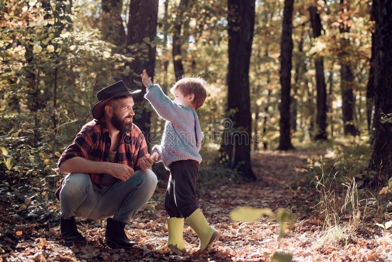 Brutalny brodaty mężczyzna i chłopiec cieszymy się jesieni naturę Rodzinny czas wolny Warto?ci rodzinne Bada natur? Podr??omanii  zdjęcie royalty free