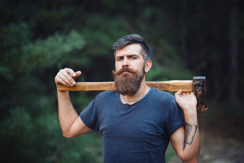 Brutalny brodaty mężczyzna z mądrze wąsy z ax w jego rękach w drewnach fotografia stock