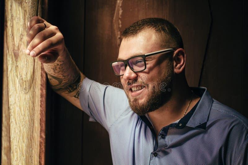 Brutalny brodaty mężczyzna z tatuażem na jego ręce, portret mężczyzna w dramatycznym świetle przeciw brown drewnianej ścianie, at zdjęcia stock