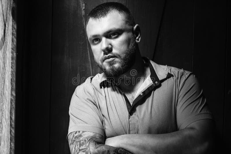 Brutalny brodaty mężczyzna z tatuażem na jego ręce, portret mężczyzna w dramatycznym świetle przeciw brown drewnianej ścianie, br obrazy stock