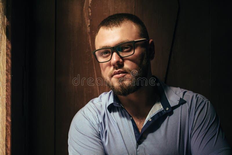 Brutalny brodaty mężczyzna z tatuażem na jego ręce, portret mężczyzna w dramatycznym świetle przeciw brown drewnianej ścianie, br fotografia royalty free