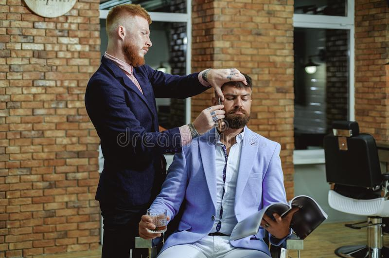 Brutalny facet w nowożytnym fryzjera męskiego sklepie Fryzjer robi fryzurze mężczyzna z brodą Portret elegancka mężczyzna broda m fotografia stock